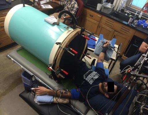Imagen: Voluntarios del estudio en la cámara que imita los efectos de la pérdida de sangre (Fotografía cortesía de Blair Johnson, Universidad de Buffalo).