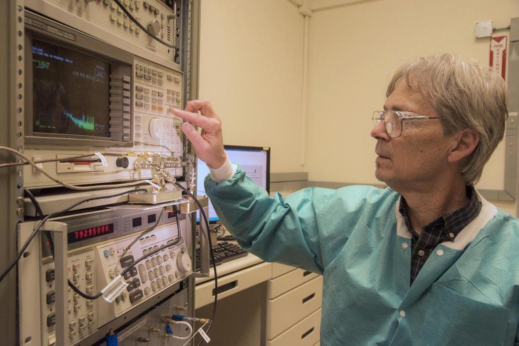 Imagen: El Dr. Ward Johnson observa las señales generadas por las bacterias que recubren los cristales de cuarzo (Fotografía cortesía de Burrus / NIST.