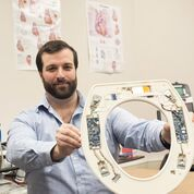 Imagen: Nicholas Conn presenta el sistema de monitorización cardiovascular basado en el asiento del inodoro (Fotografía cortesía de Sue Weisler/RIT).