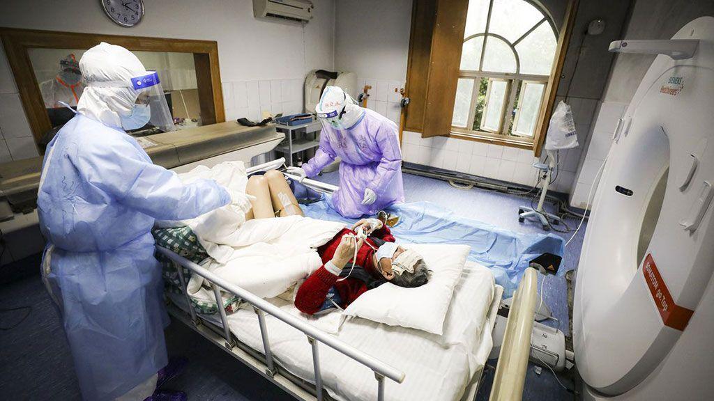 Imagen: Trabajadores hospitalarios en China mientras preparan a un paciente con COVID-19 para una TC (Fotografía cortesía de Getty Images)