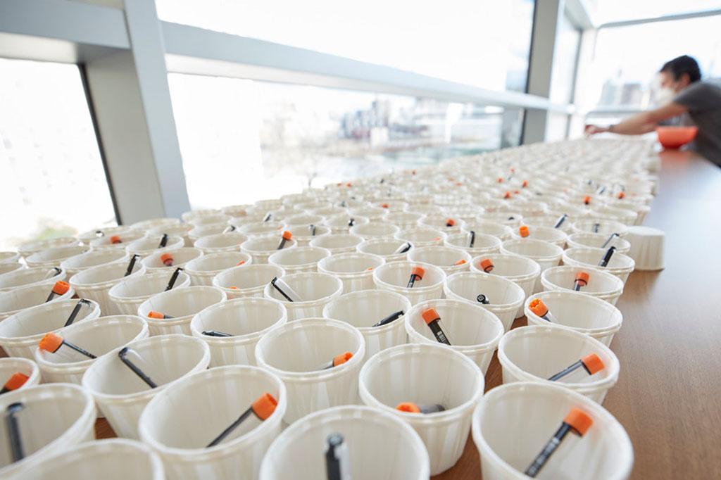 Imagen: Almacenado en viales con tapa naranja para distribución masiva, el tampón DRUL es parte de una prueba COVID en saliva de bajo costo desarrollada en Rockefeller (Fotografía cortesía de la Universidad Rockefeller)