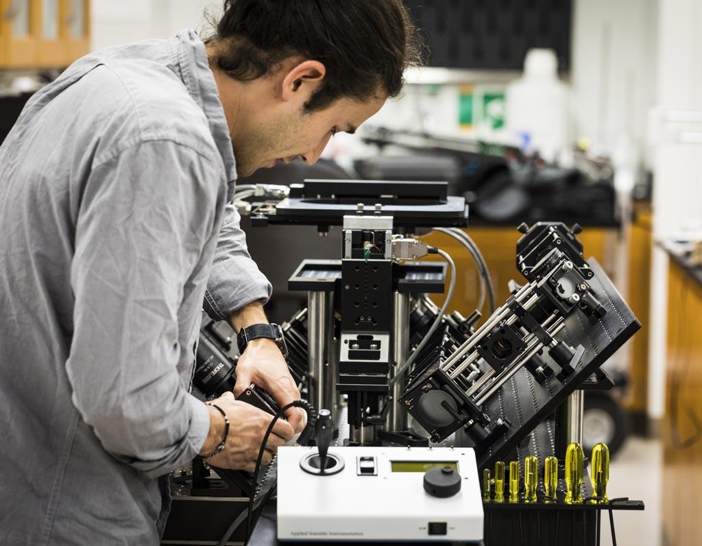 Imagen: Un científico ajustando el microscopio de iluminación de planos selectivos que puede proporcionar a cirujanos los datos en tiempo real de la patología para dirigir las cirugías de extirpación del cáncer y también puede examinar las biopsias de los tumores en 3D, de manera no destructiva (Fotografía cortesía de Mark Stone/Universidad de Washington).