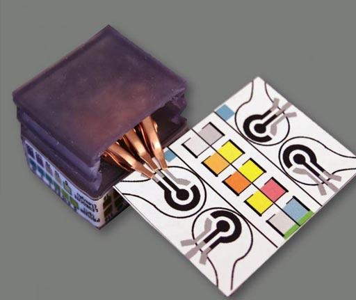 Imagen: Dispositivo de diagnóstico de papel que detecta biomarcadores e identifica las enfermedades mediante la realización de análisis electroquímicos. Los ensayos cambian de color para indicar los resultados de las pruebas específicas. El dispositivo se puede conectar al potenciostato de mano, a la izquierda (Fotografía cortesía de la Universidad de Purdue, Aniket Pal).