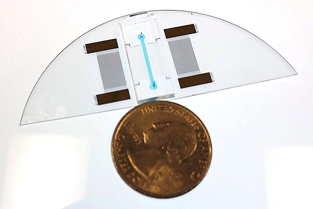 """Imagen: Se muestra un dispositivo """"lab-en-un-chip"""" para un Análisis de Desplazamiento Térmico Acústico, junto a una moneda de un cuarto de dólar estadounidense para comparar el tamaño. El dispositivo puede diagnosticar la anemia de células falciformes (Fotografía cortesía de la Facultad de Ingeniería y Ciencias Aplicadas de la CU Boulder)."""
