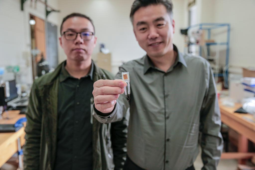 Image: Graduate student Guang Yao (L) and Professor Xudong Wang (R) with the implantable device (Photo courtesy of Sam Million-Weaver/ WISC).