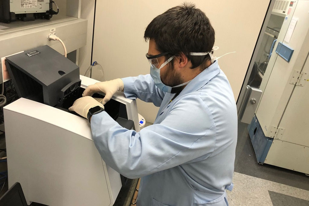 Image: Sean Paz, co-author and a graduate student in FAU's Schmidt College of Medicine, loads COVID-19 tests in a PCR (polymerase chain reaction) machine (Photo courtesy of FAU).