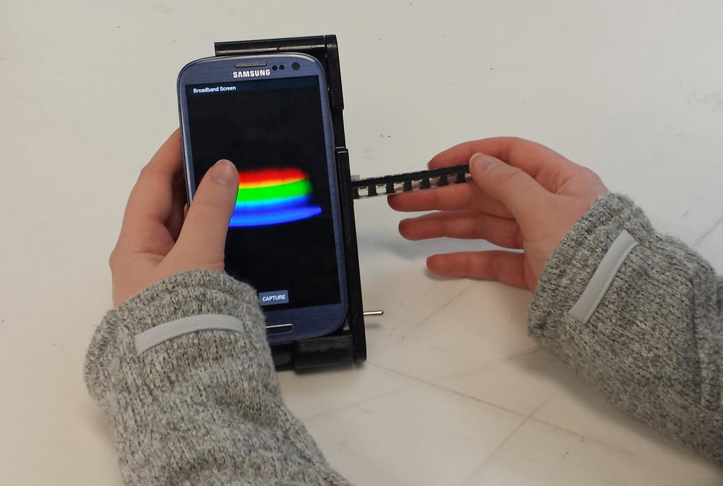 Image: The spectral transmission-reflectance-intensity (TRI)-Analyzer attaches to a smartphone and analyzes patient blood, urine, or saliva samples as reliably as clinic-based instruments that cost thousands of dollars (Photo courtesy of the Department of Bioengineering, University of Illinois at Urbana-Champaign).