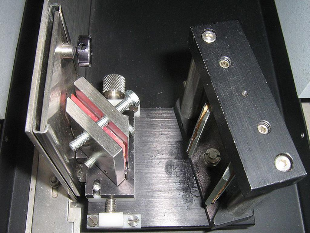Image: An ATR attachment for infrared spectroscopy. The sample is in the steel containers either side of the pink crystal (Photo courtesy of Wikimedia Commons).