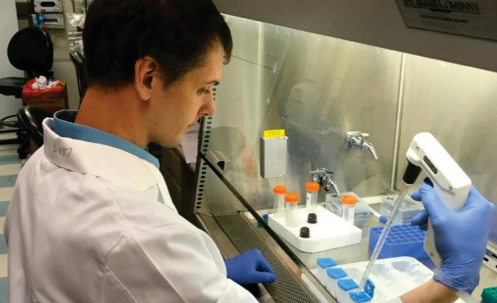 Image: A scientist assembling the cartridge assay that distinguishes cancer from benign aspirates from mammographically suspicious breast lesions (Photo courtesy of Wanjun Ding).