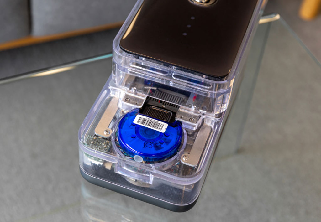 Image: The blue circular CovidNudge cartridge inside the NudgeBox analyzer (Photo courtesy of Imperial College London)