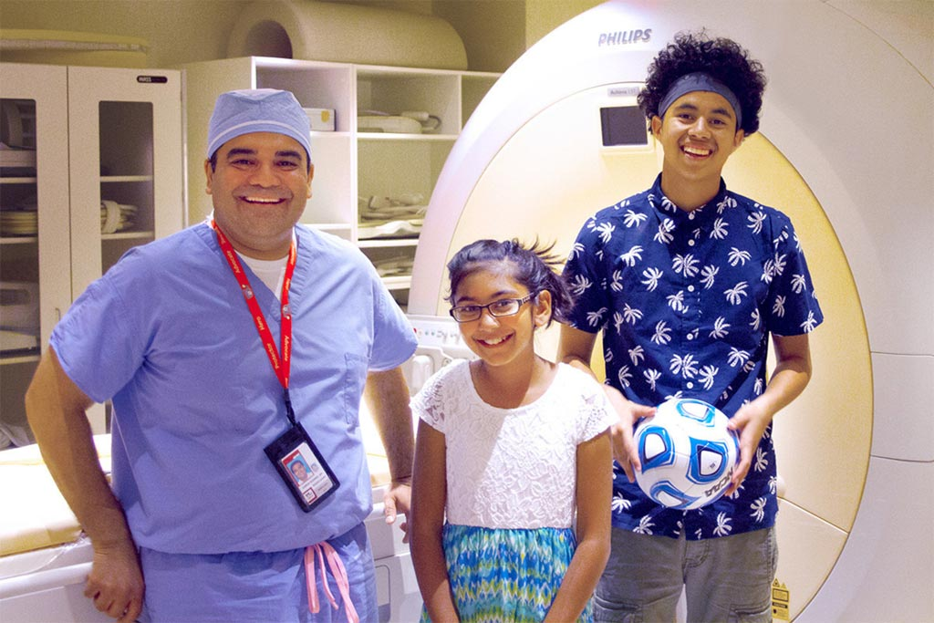 Image: Karun Sharma, MD, PhD, director of Interventional Radiology, Children\'s National Health System, with two children who were treated for osteoid osteoma using the non-invasive MR-HIFU technique (Photo courtesy of Cision CR Newswire).
