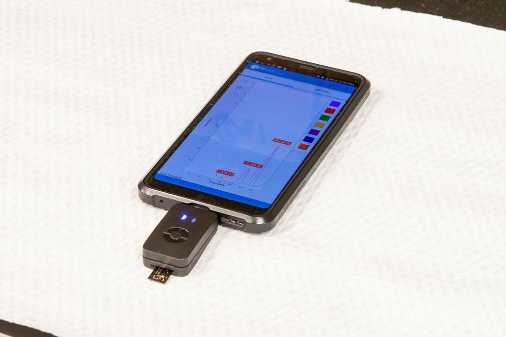 Imagen: Un dispositivo de código de barras biológico, electroquímico, desarrollado recientemente junto con un teléfono inteligente permite a los pacientes con cáncer leer niveles críticos de biomarcadores en casa en muestras de sangre extraídas por ellos mismos (Fotografía cortesía de Georgia Kirkos, Universidad McMaster)