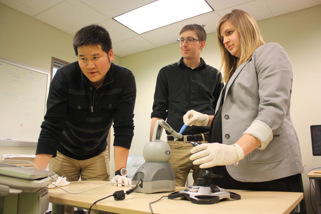 Image: Dr. Scarlett Miller demonstrating the prototype haptic robotic training system (Photo courtesy of Shea Winton/ PSU).