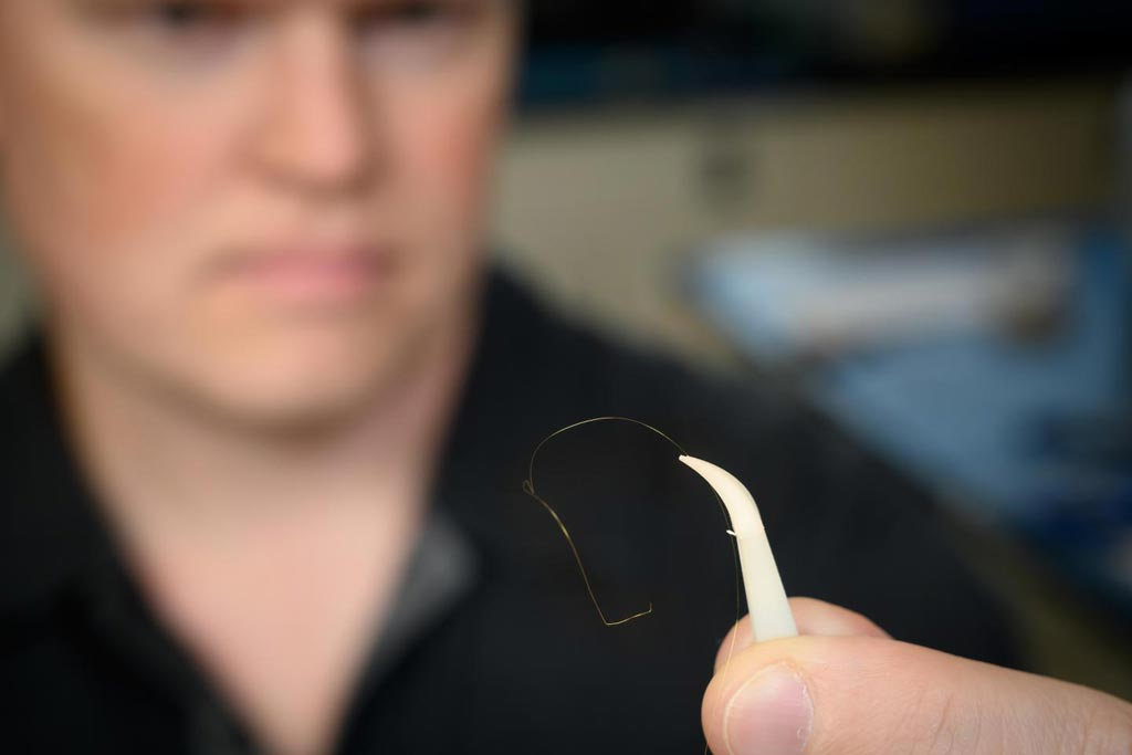 Image: Dr. Brian Geiss displays a gold microwire that is one-fourth the size of a human hair (Photo courtesy of John Eisele, Colorado State University Photography).