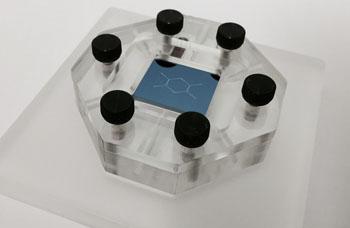 Чип nano-DLD (2х2 см), установленный в микрожидкостное устройство. Технология позволяет жидкому образцу непрерывно протекать через кремниевый чип, содержащий массив асимметричных столбиков, который сортирует микроскопический водопад наночастиц, отделяющий частицы по размеру с разрешением до 20 нанометров (фото любезно предоставлено Исследовательским центром IBM имени Томаса Джона Уотсона).